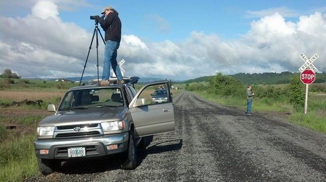 Doug Robinson standing on the roof of a truck taking bird photos