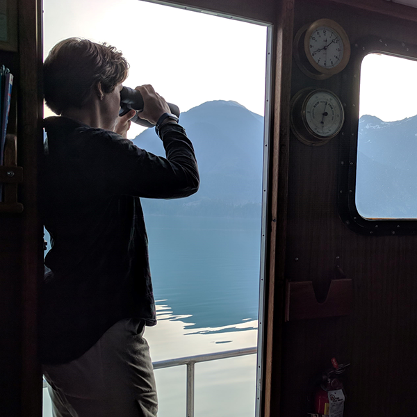 Woman on a boat using binoculars to look out over the water
