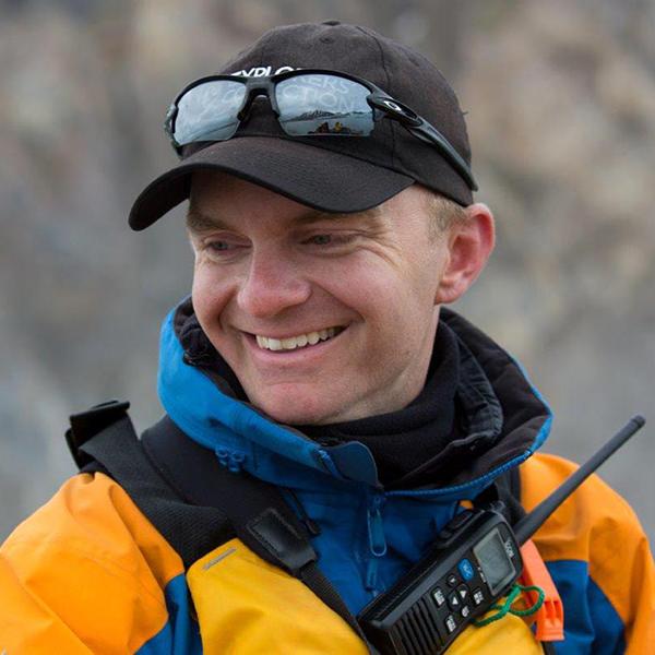 Man in orange jacket smiling